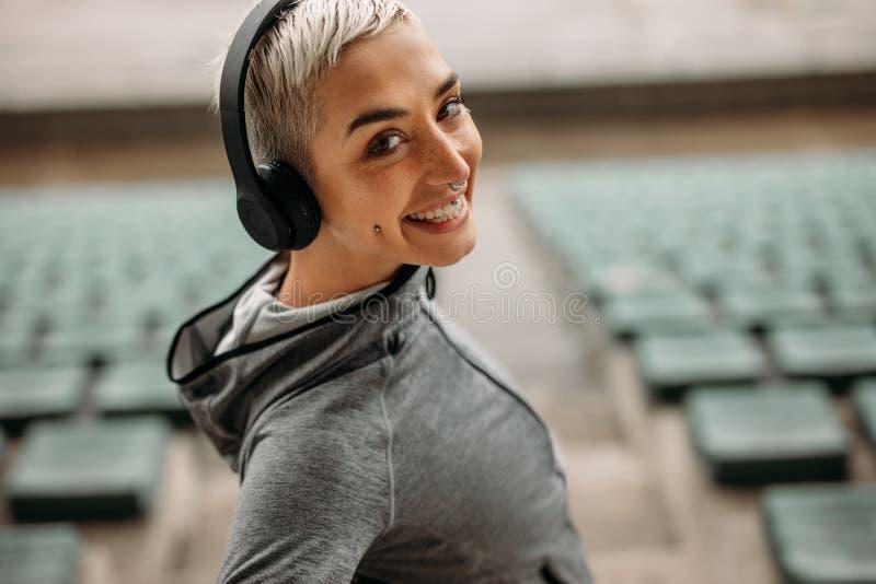 Sluit omhoog van een glimlachende vrouw die zich in een stadion bevinden stock afbeelding