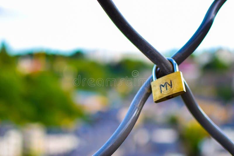 Sluit omhoog van een gouden hangslot met de brieven van M en V-, met een vage kleurrijke achtergrond stock foto's