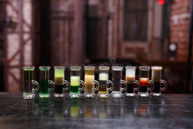 Sluit omhoog van een groep diverse alcoholische cocktails op houten die teller, op een rode achtergrond van barlichten wordt geïs royalty-vrije stock afbeelding