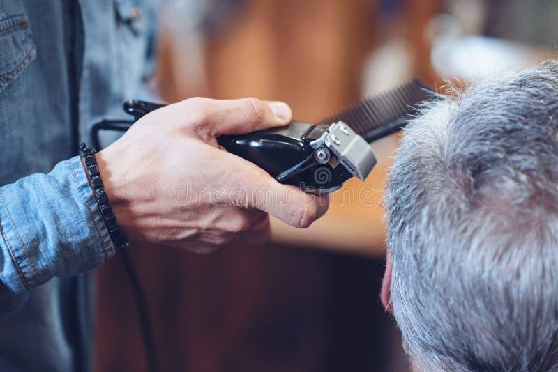 Sluit omhoog van een haarsnijmachine die in kappershanden zijn stock foto
