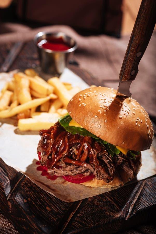 Sluit omhoog van een hamburger die met Frieten worden gediend stock afbeeldingen