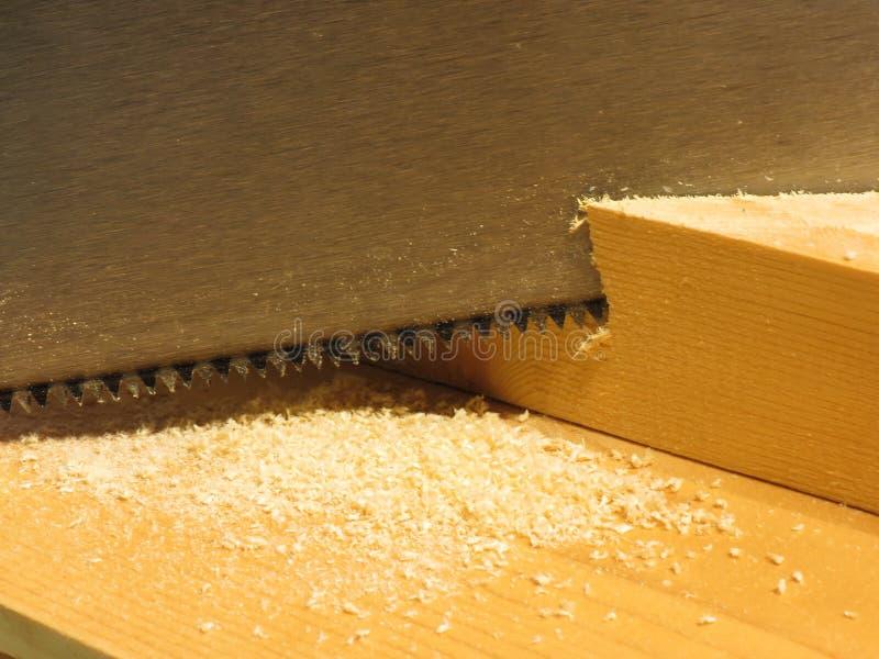 Sluit omhoog van een handzaag snijdend een stuk van hout op het houten werk royalty-vrije stock foto's