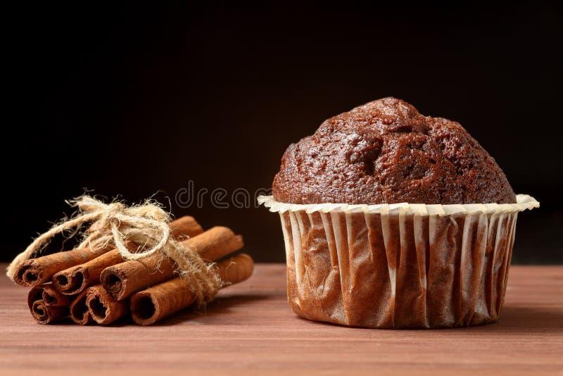 Sluit omhoog van een heerlijke chocolademuffin met pijpjes kaneel op een houten lijst tegen zwarte achtergrond Ruimte voor tekst stock foto