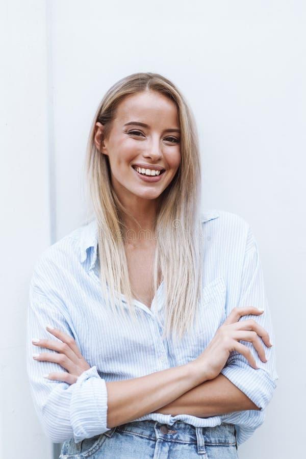 Sluit omhoog van een het glimlachen jonge blondevrouw status stock afbeelding