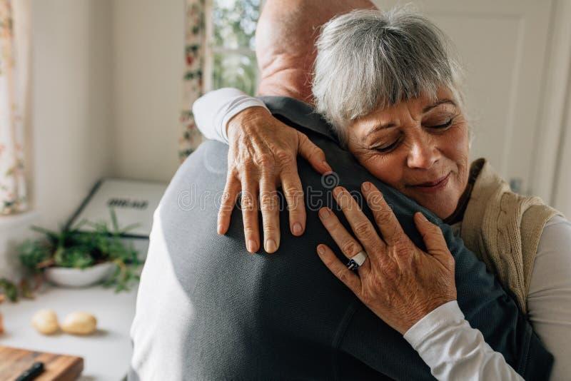 Sluit omhoog van een hogere vrouw omhelzend haar echtgenoot met gesloten ogen die zich in keuken bevinden Bejaard paar die elkaar royalty-vrije stock foto's