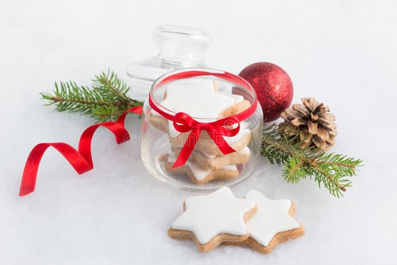 Sluit omhoog van een hoogtepunt van de glaskruik met koekjes van de Kerstmis de eigengemaakte ster over witte pluizige achtergron stock fotografie
