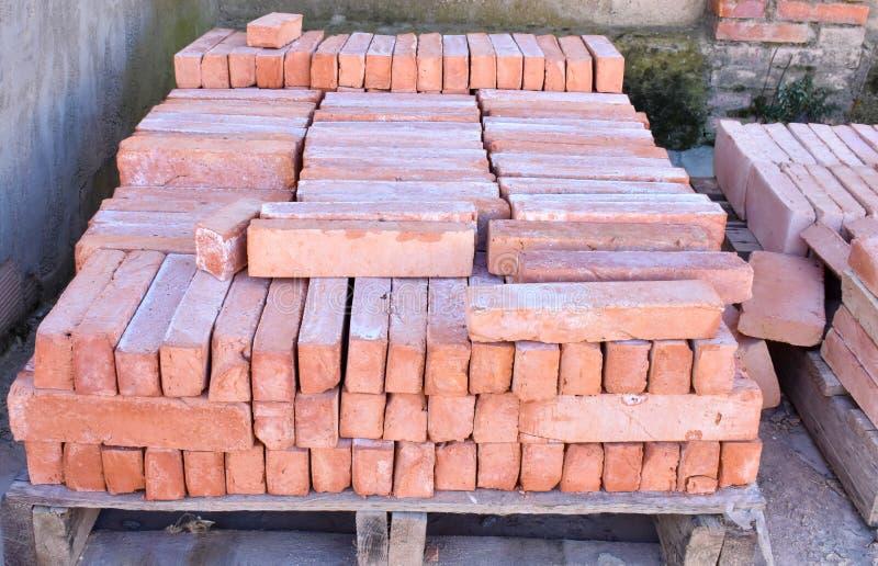Sluit omhoog van een houten palletovervloed van oude gestapelde rode bakstenen De bakstenen worden bevolen in vele rijen royalty-vrije stock afbeeldingen