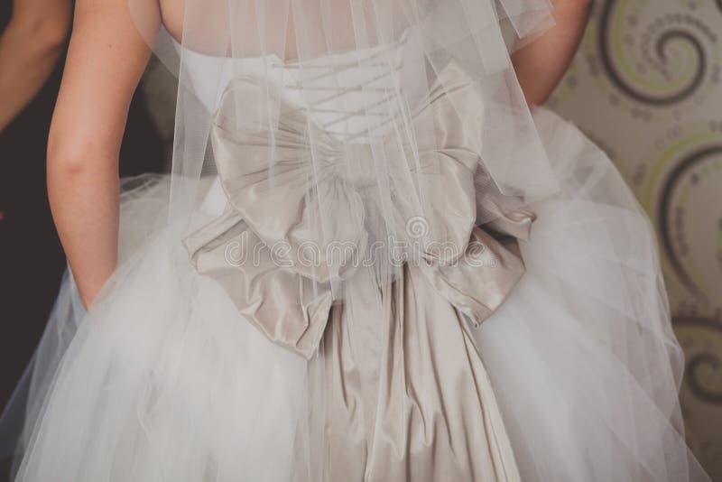 Sluit omhoog van een huwelijkskleding met grote zijdeboog stock fotografie