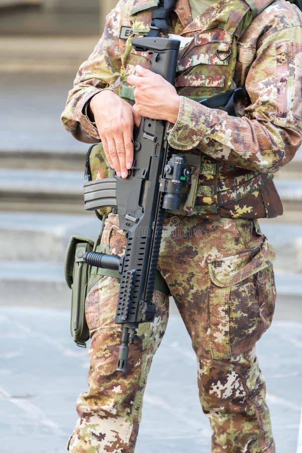 Sluit omhoog van een Italiaanse militair in een stad met een automatisch geweer, het concept van de noodsituatiestaat stock afbeelding