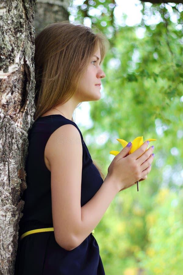 Sluit omhoog van een jong meisje die gele bloem buiten ruiken stock afbeelding