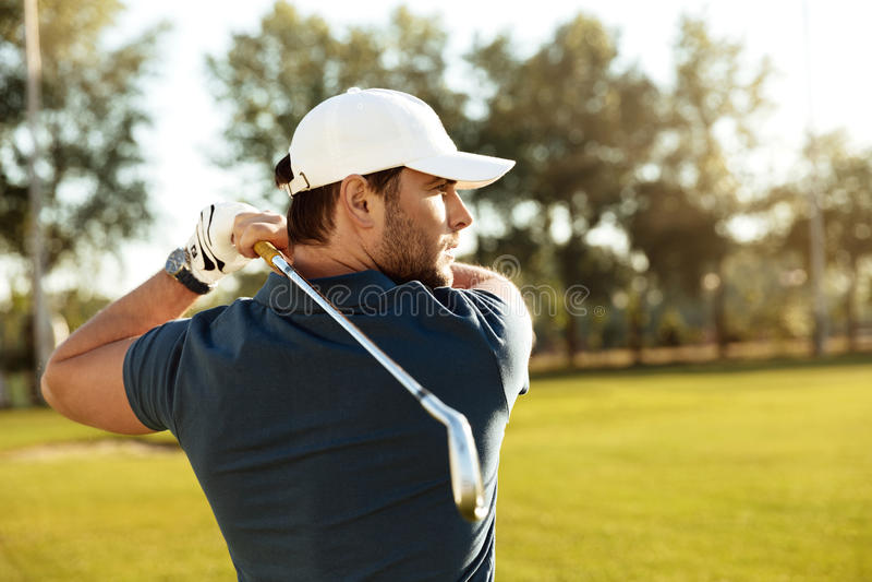 Sluit omhoog van een jonge geconcentreerde mens die golfbal schieten royalty-vrije stock afbeeldingen