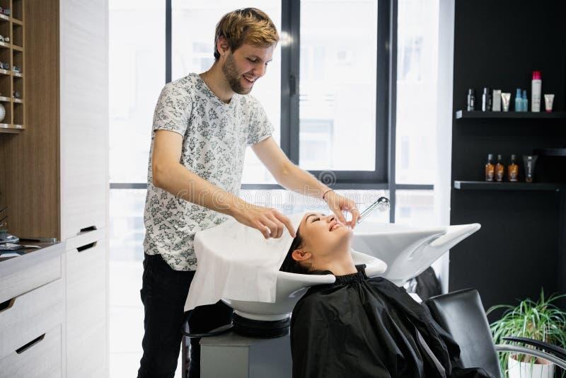 Sluit omhoog van een jonge gelukkige mooie vrouw die aan de camera glimlachen terwijl professionele kapper die haar nat haar binn stock afbeeldingen
