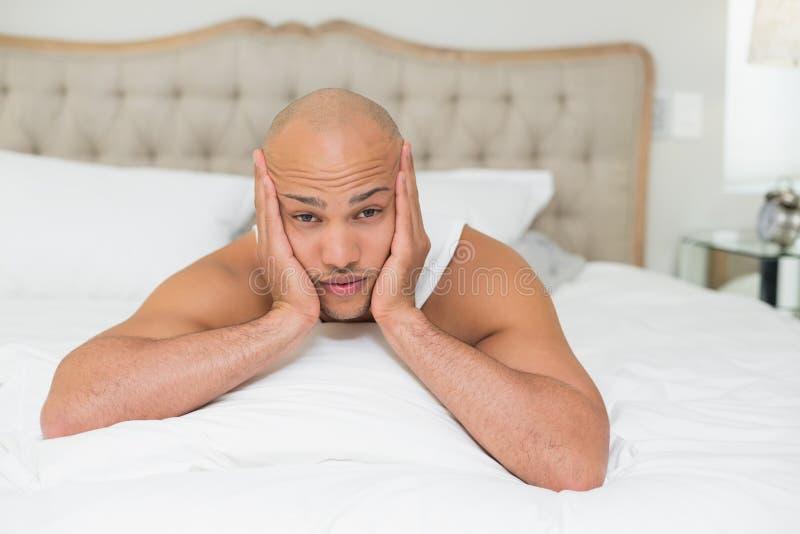 Sluit omhoog van een jonge mens die in bed rusten royalty-vrije stock fotografie