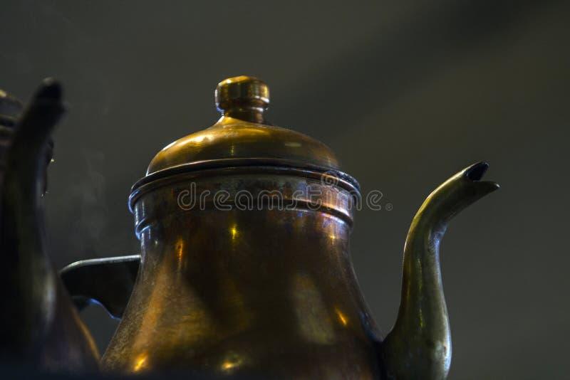 Sluit omhoog van een koper gemaakt uitstekende tot theepot met details op zijn spuiten, deksel, knop, schouder en buik royalty-vrije stock afbeelding