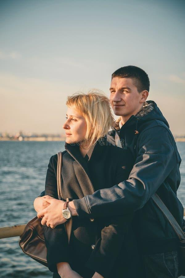 Sluit omhoog van een leuk jong mooi paar die bij pijler bij zonsondergang, mens zijn meisje koesteren zacht, hipster, gelukkige o royalty-vrije stock fotografie
