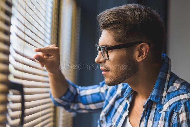 Sluit omhoog van een mens die door zonneblinden kijken stock fotografie