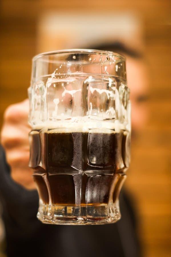 Sluit omhoog van een mens die een donker bier dolding, brouwt de heerlijke Sterke drank van het ambachtbier Alcohol viert royalty-vrije stock fotografie