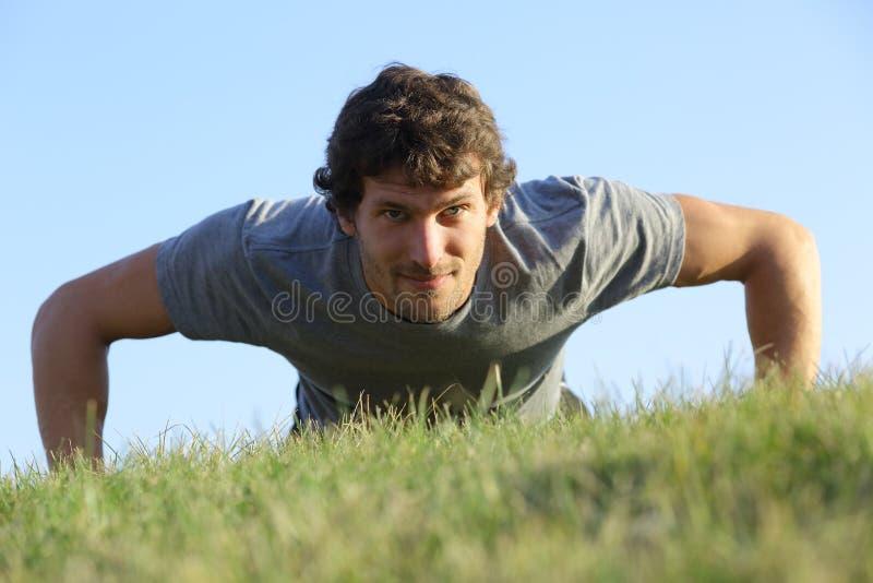 Sluit omhoog van een mens die opdrukoefeningen op het gras doen stock fotografie