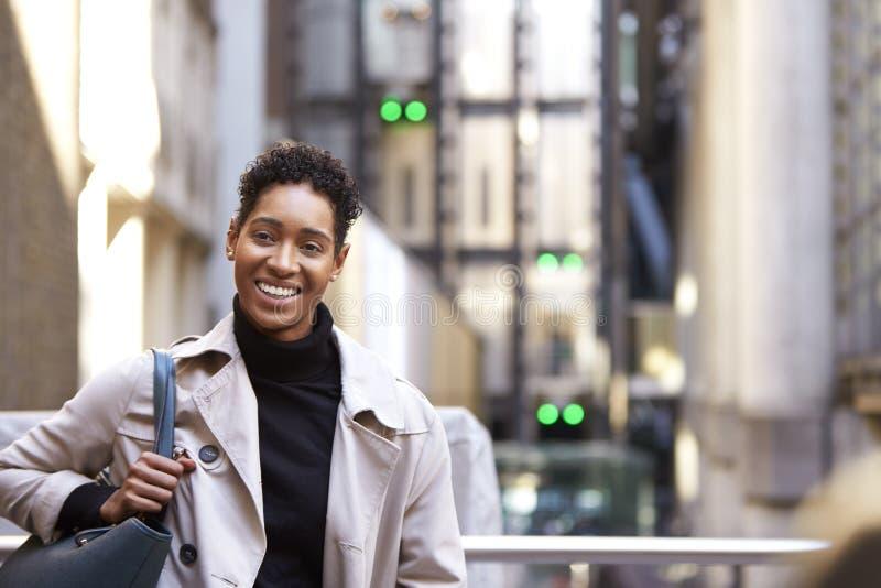 Sluit omhoog van een millennial zwarte onderneemster die zich op een straat in Londen bevinden aan camera, taille omhoog glimlach stock afbeelding