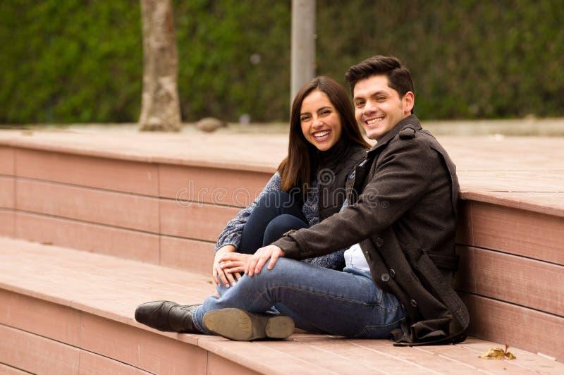 Sluit omhoog van een mooi glimlachend jong paar in liefde in st valentijnskaartendag en het bekijken camera, zittend in een park royalty-vrije stock afbeeldingen