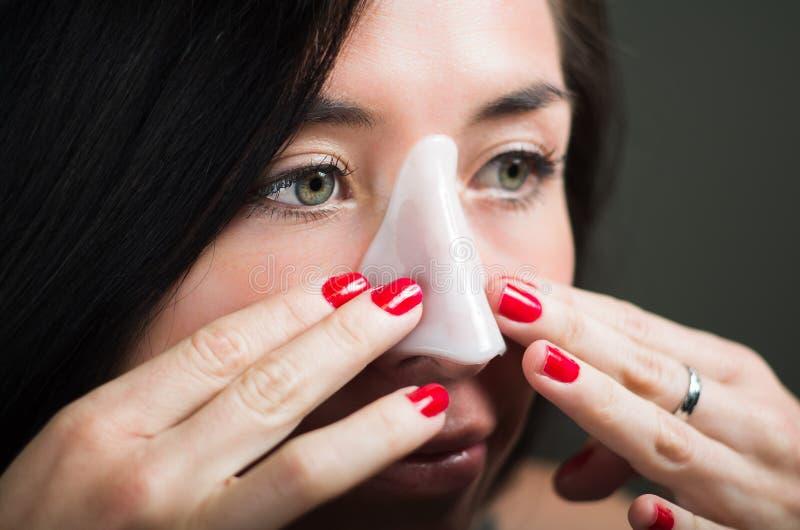 Sluit omhoog van een mooie jonge vrouw die een wit neusmasker aplying om de huid schoon te maken stock afbeeldingen