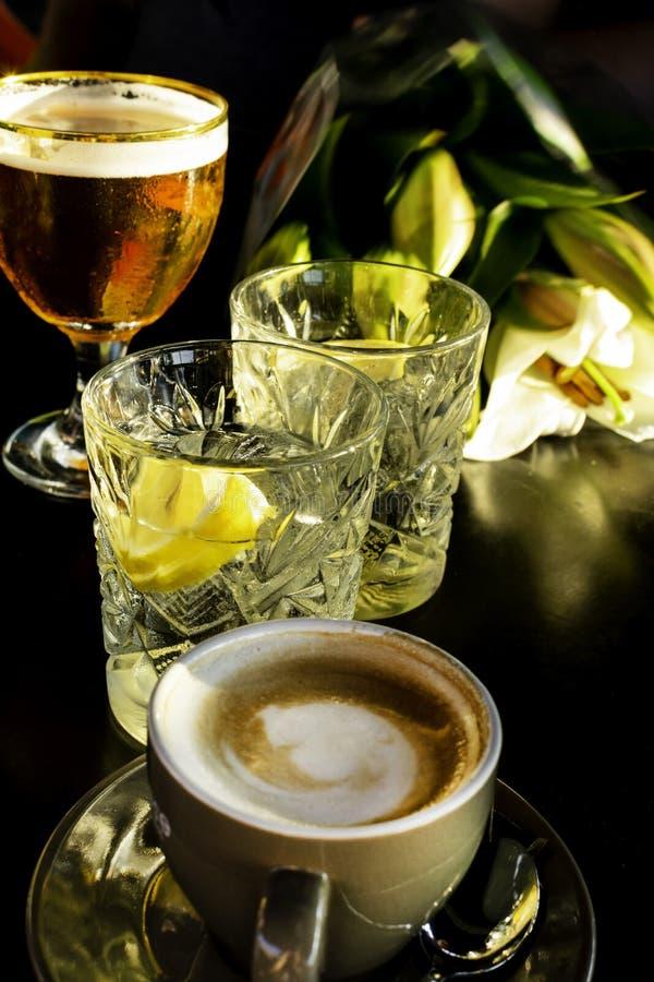 Sluit omhoog van een nat glas koud bier, martini met citroenplakken, kop van koffie Selectieve nadruk royalty-vrije stock foto