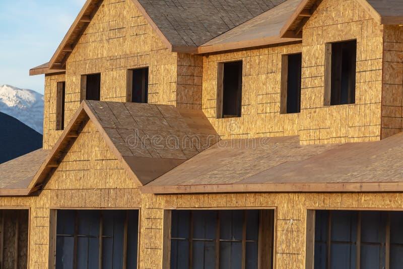 Sluit omhoog van een nieuw huis buiten met onvolledige muurdak en vensters stock afbeeldingen