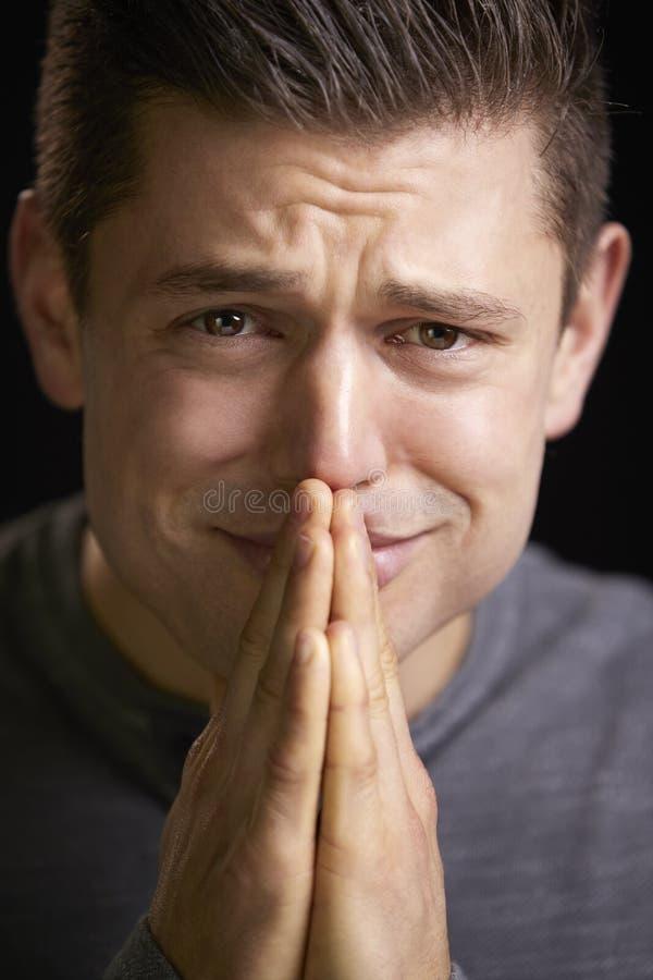 Sluit omhoog van een ongerust gemaakte jonge mens met handen clasped, verticaal royalty-vrije stock foto