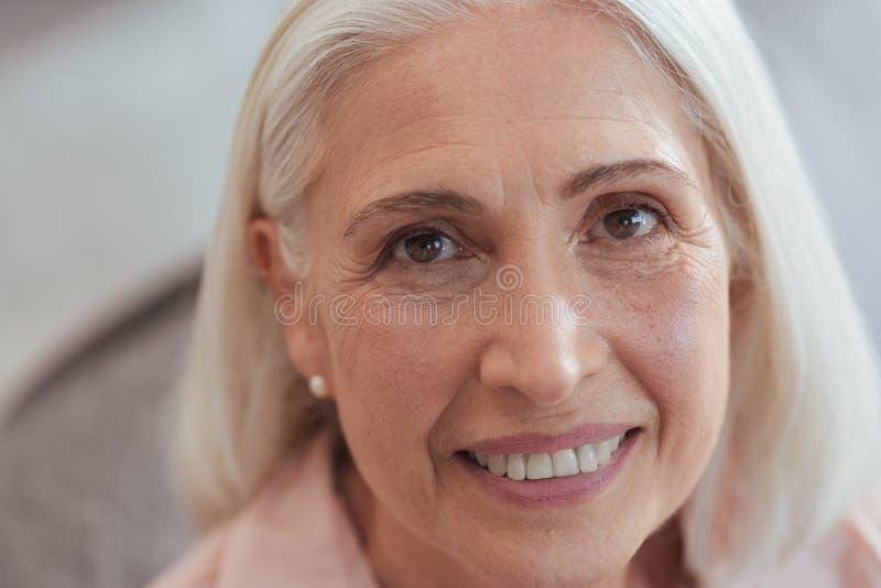Sluit omhoog van een open gelete op oude glimlachende vrouw stock afbeelding