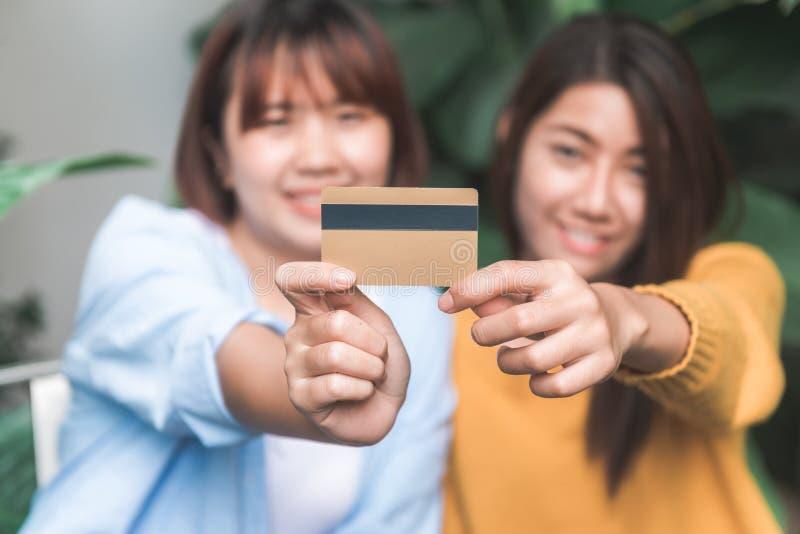 Sluit omhoog van een paar jonge Aziatische vrouwen gebruikend haar creditcard terwijl zij het winkelen online met haar laptop doe stock foto's