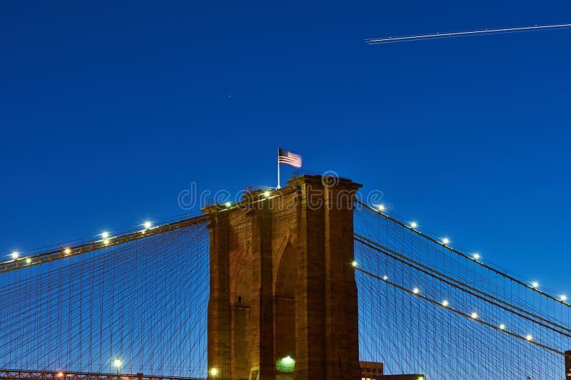 Sluit omhoog van een pijler van de brug van Brooklyn met vlag bij nacht royalty-vrije stock fotografie