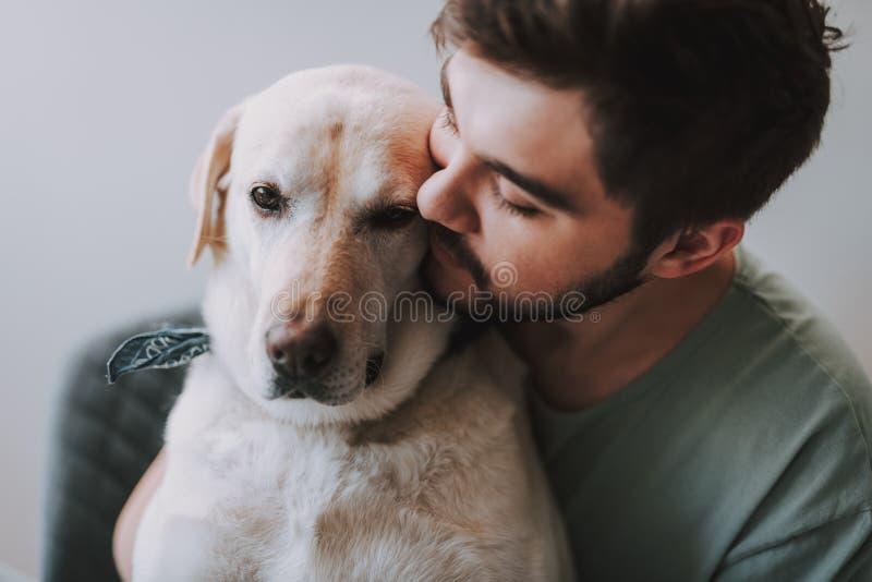 Sluit omhoog van een prettige mens die zijn hond kussen stock foto's