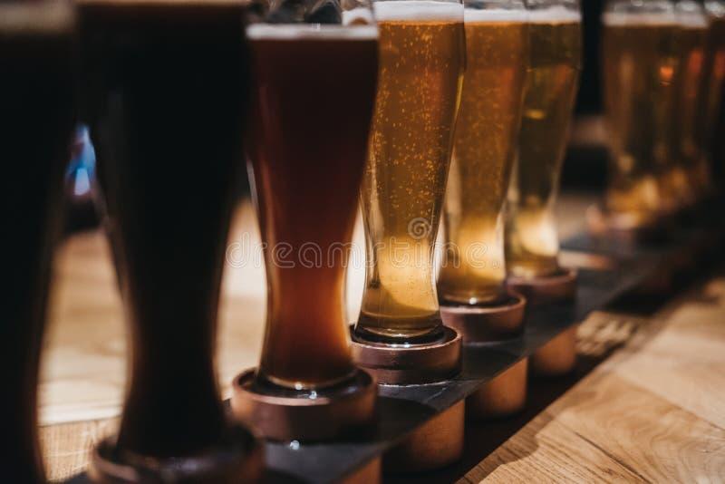 Sluit omhoog van een rek van verschillende soorten bieren, donker aan licht, op een lijst royalty-vrije stock foto's