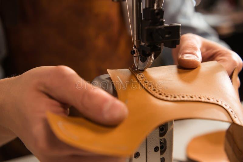 Sluit omhoog van een schoenmaker die een deel van schoen stikken stock fotografie