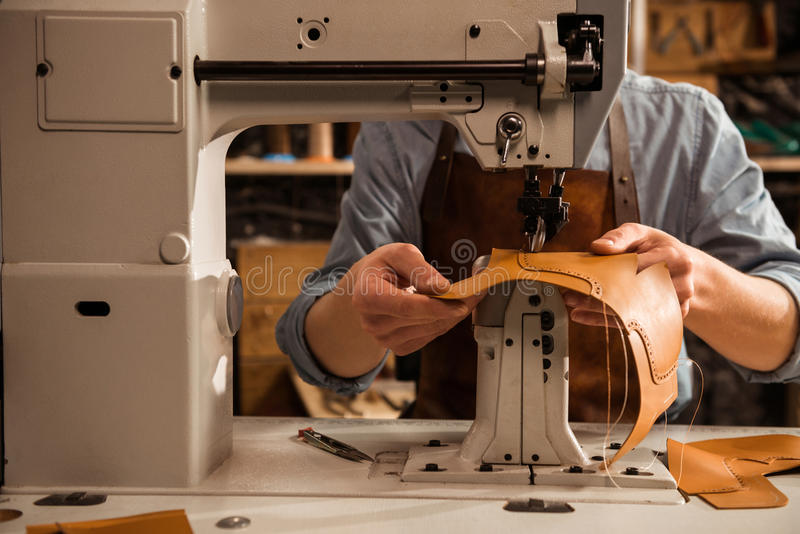 Sluit omhoog van een schoenmaker gebruikend naaimachine stock afbeelding