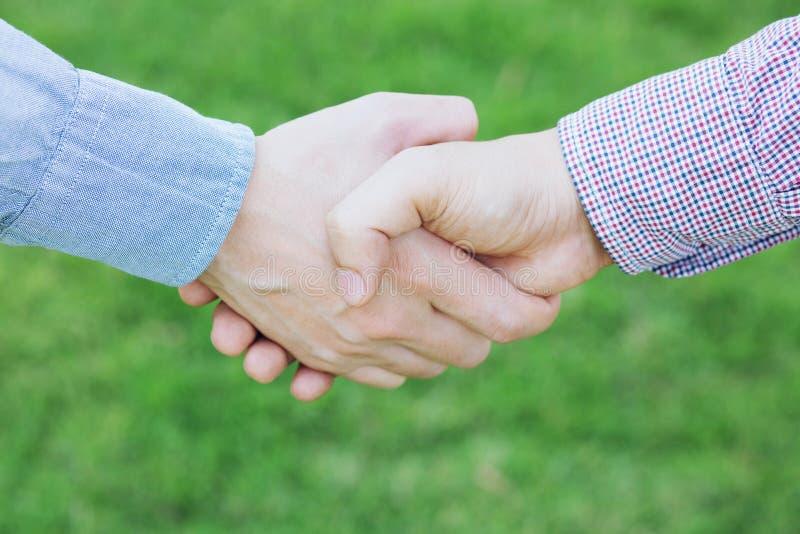 Sluit omhoog van een schok van de bedrijfsmensenhand tussen twee collega's begroeten stock afbeelding