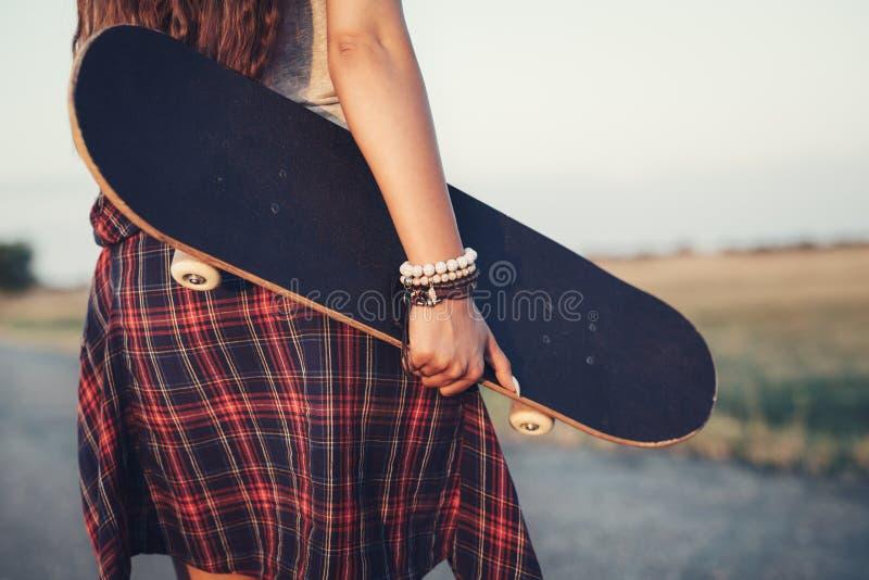 Sluit omhoog van een skateboard van de tienerholding stock foto