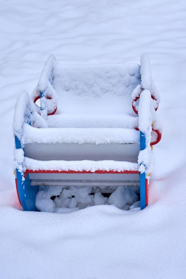 Sluit omhoog van een sneeuw behandelde boot gestalte gegeven geschommelwipplank wankelen in een park van het kinderenspel tijdens stock foto's