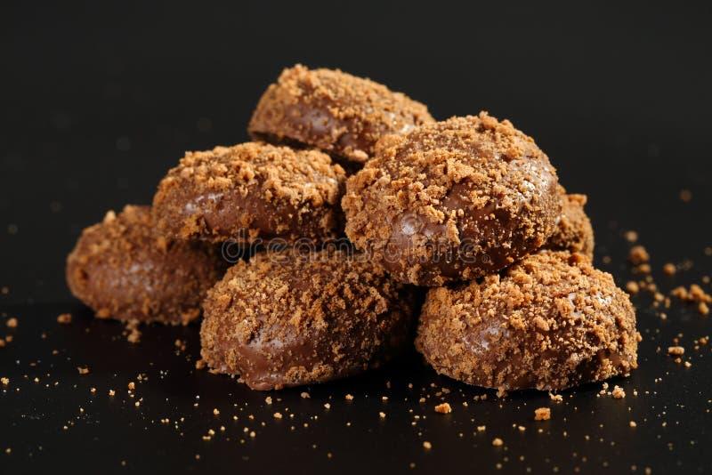 Sluit omhoog van een stapel van heerlijke knapperige die karamelkoekjes met melkchocola en koekjesdeeltjes met een laag worden be stock foto