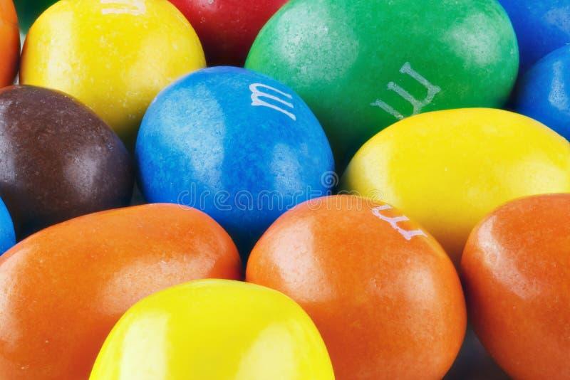 Sluit omhoog van een stapel van kleurrijk met chocolade bedekt suikergoed, chocoladepatroon, suikergoedachtergrond, hoogste menin stock foto