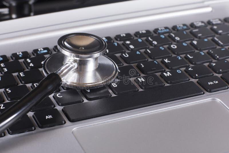 Sluit omhoog van een stethoscoopschijf op laptop royalty-vrije stock foto