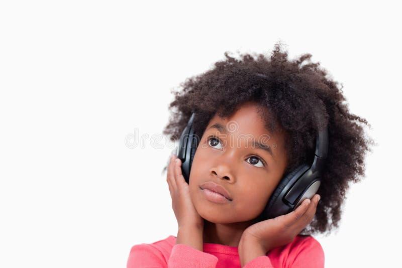 Sluit omhoog van een stil meisje dat aan muziek luistert royalty-vrije stock afbeelding