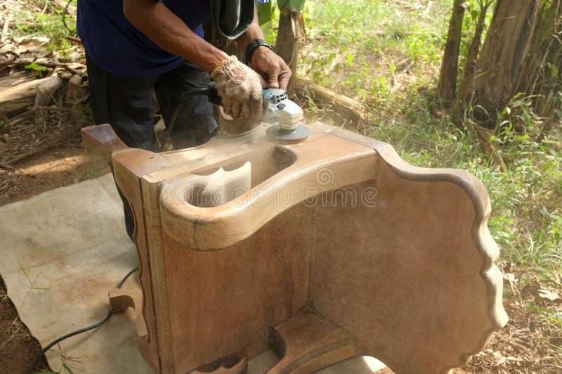 Sluit omhoog van een timmerman die houten stoel met handbediende elektrische gaszuiveraar schrobben stock foto's