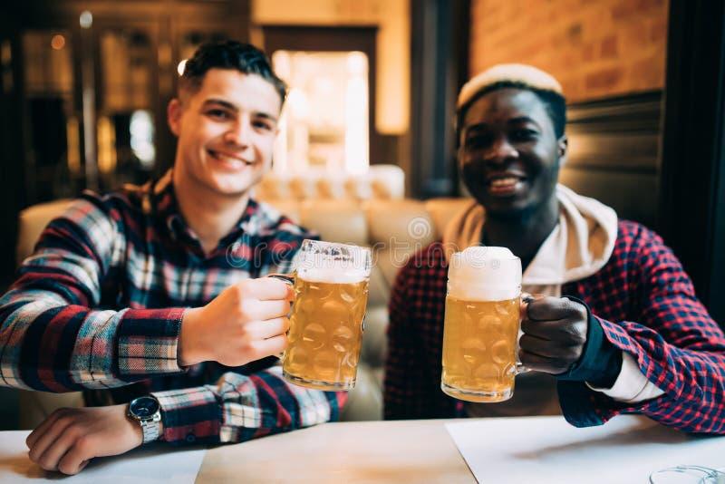 Sluit omhoog van een twee gelukkige mensenvrienden die bier drinken bij bar of bar stock afbeeldingen
