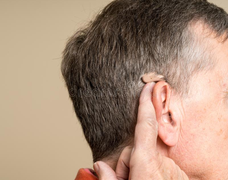 Sluit omhoog van een uiterst klein modern gehoorapparaat achter oor royalty-vrije stock afbeelding