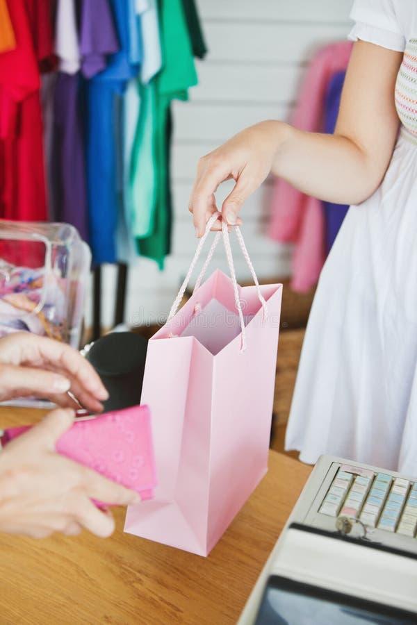 Sluit omhoog van een verkoopster en een vrouwelijke klant royalty-vrije stock afbeelding