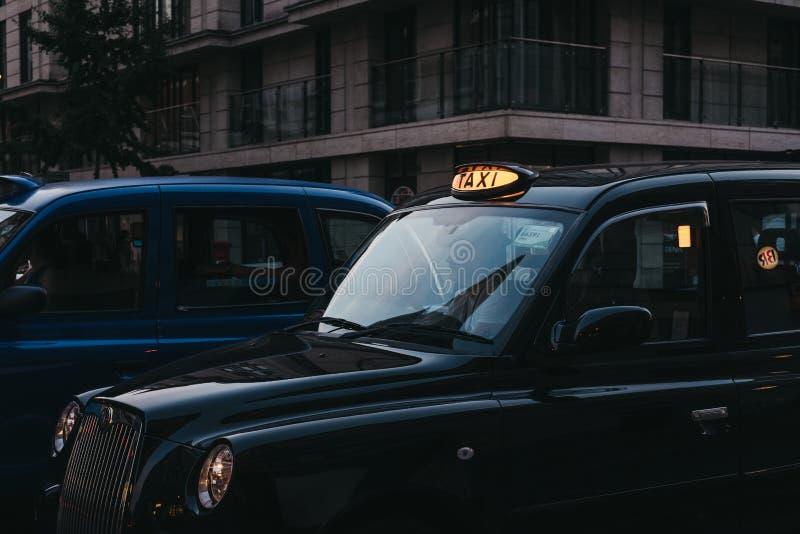 Sluit omhoog van een verlicht taxiteken op een zwarte cabine in Londen, U royalty-vrije stock foto's
