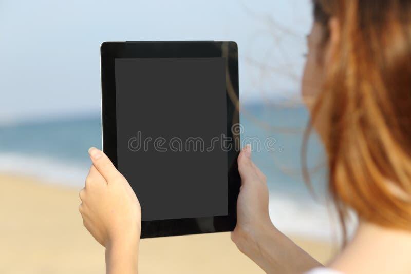 Sluit omhoog van een vrouw die het leeg tabletscherm op het strand tonen stock fotografie