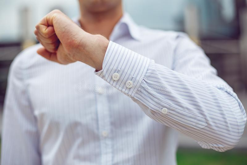 Sluit omhoog van een zakenman in een wit overhemd en toont de koker stock foto's