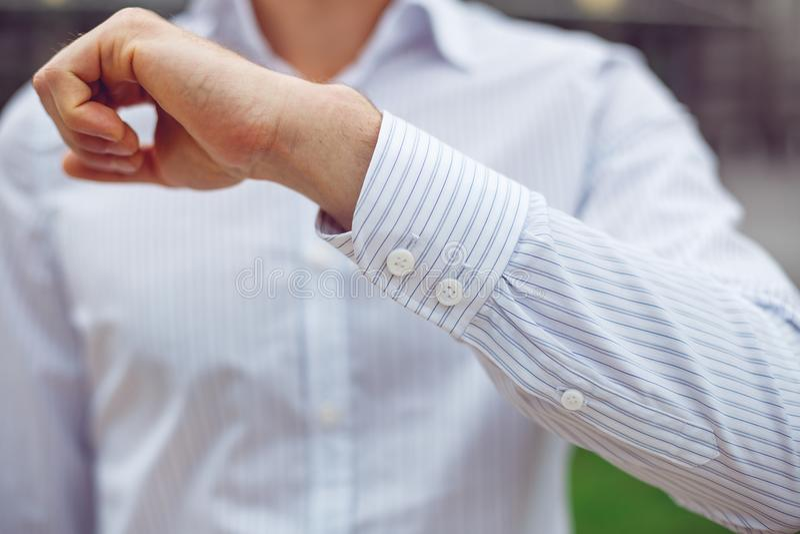 Sluit omhoog van een zakenman in een wit overhemd en toont de koker stock afbeeldingen